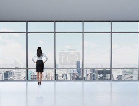 Rear view of brunette woman in the office who looks through the window. New York panoramic office. A concept of a successful woman in a business._高清图片_邑石网