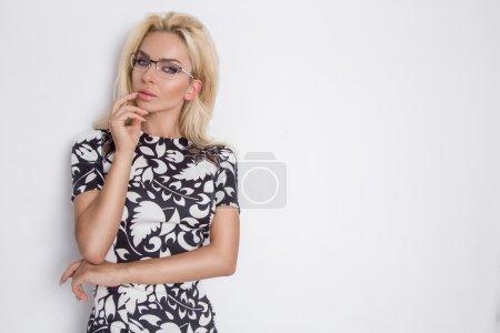 绿色的眼睛在眼镜中的白衣黑优雅性感短裙和白色的裤子,白色的背景上美丽茂盛的卷曲金发性感模型