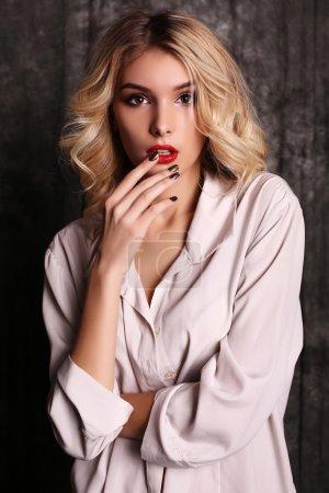 美丽的女人,与金发卷曲的头发和晚上化妆,穿件白衬衫