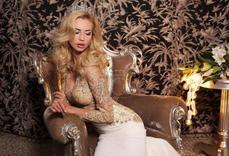 金发的美丽女子穿着豪华婚纱和比茹