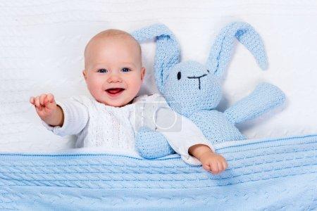 宝贝男孩玩耍着蓝色针织的兔子玩具