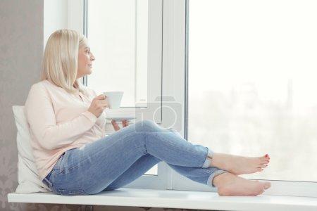 Woman sits on the windowsill