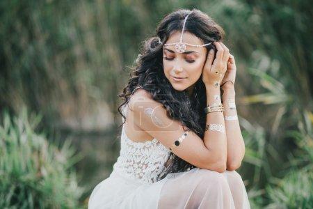 美丽的年轻女子,与构成湖附近的波西米亚风格穿着长长的卷发