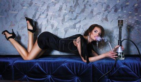 性感的派女人吸烟水烟在夜总会