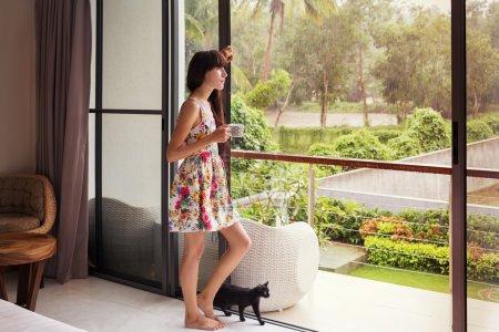 漂亮的年轻女人,附近的黑猫大窗户。