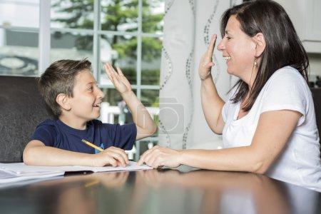 母亲帮助儿子在桌上的作业