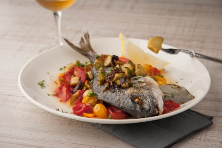 Fried dorado with vegetables on the ceramic plate with glass of vine horizontal
