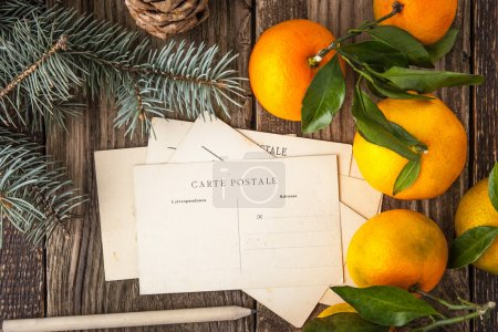Postcards with fir tree and mandarins on the wooden table