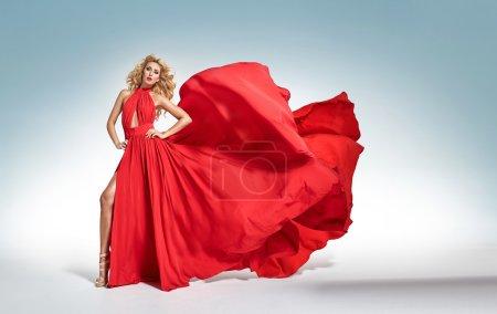 漂亮诱人的金发女郎,挥舞着衣服的红色