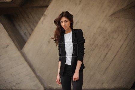 深色的年轻女人站在外面穿黑夹克,牛仔裤穿山。水平