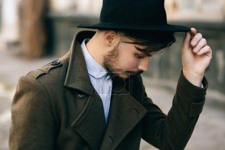在街上带着手提箱的帽子 Fedora 英俊年轻的胡子的时髦人家伙。复古复古时尚外观_高清图片_邑石网