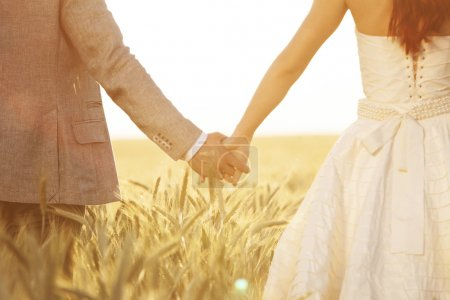 Wedding couple holding hands in field of rye