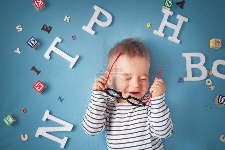 一岁的孩子躺在那儿的眼镜和字母