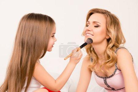 关闭了画像的女儿应用粉末在她妈妈的脸上