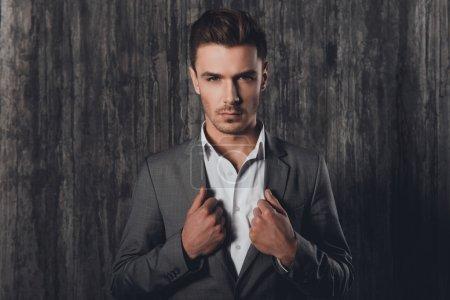 Portrait of stylish businessman touching jacket on gray backgro
