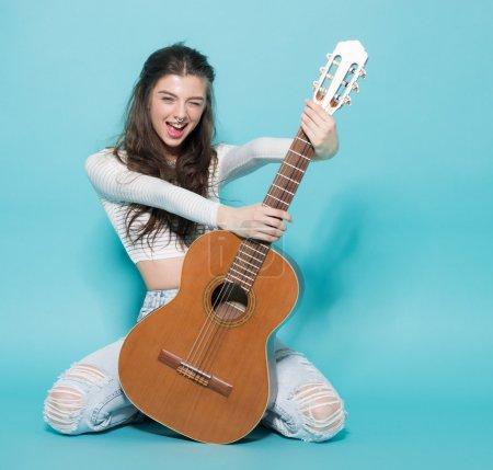 年轻漂亮的女孩与吉他合影