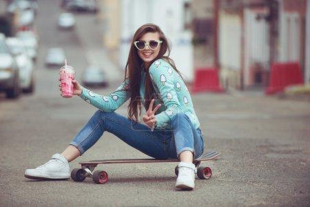 年轻漂亮的女人,和一个滑板,时尚的生活方式,在日落时的合影