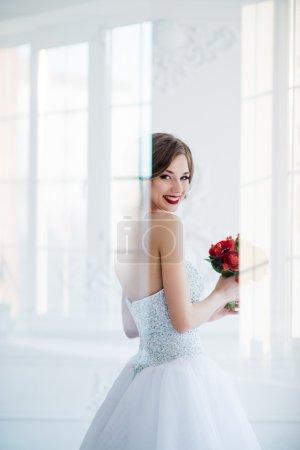 年轻和美丽时尚艺术写真的新娘穿白色连衣裙,在客厅里。透过玻璃门开枪,光创作感言覆盖肖像