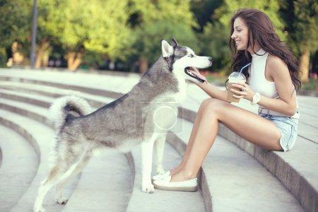 女孩喝冰咖啡和她沙哑的狗在公园里一起玩