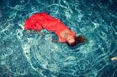 Seductive female floating on swimming pool in gorgeous red dress.