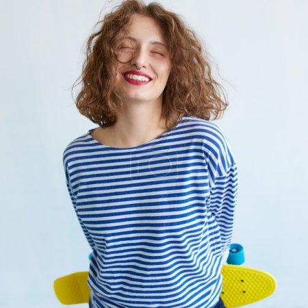 女孩抱着鲜艳的色彩滑板
