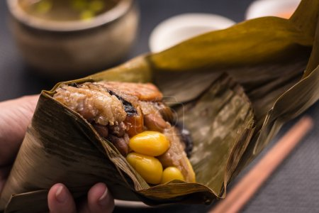 Freshly cooked Zongzi wrapped with bamboo leaf holding