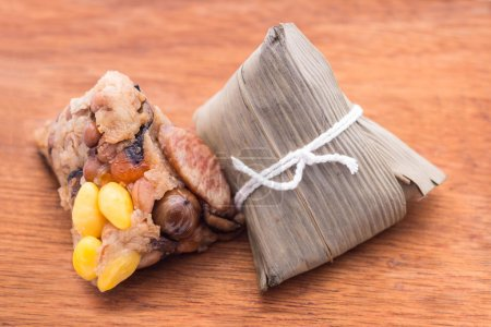 Two Zongzi or Asian Chinese sticky rice dumplings on wooden back