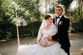 优雅的年轻快乐新婚夫妇坐在绿草