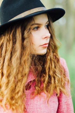 肖像年轻优雅的女人的粉红色上衣和黑色的帽子。时尚_高清图片_邑石网